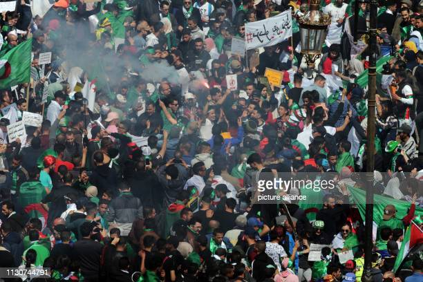 People march with flags and placards during a protest against President Abdelaziz Bouteflika's decision to withdraw from and postpone the...