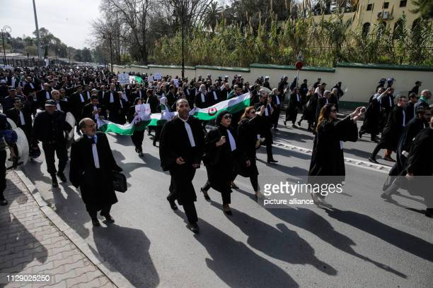 Protesters march during in a demonstration organized by Algerian lawyers outside the Constitutional Council to protest against the candidacy of...
