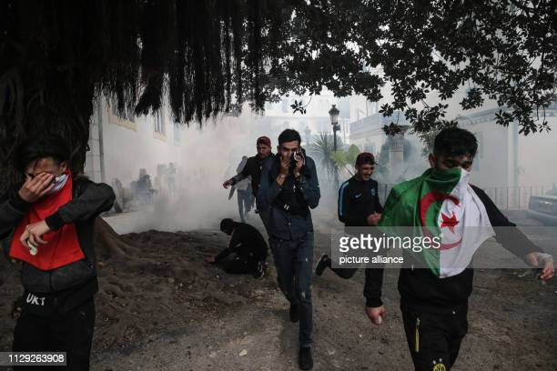 Protestors demonstrating against Algerian President Abdelaziz Bouteflika cover their faces a protection from tear gas during clashes with Algerian...
