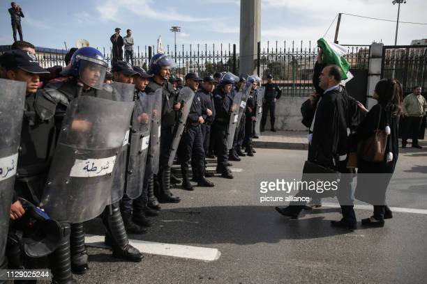 Riot police face protesters during a demonstration organized by Algerian lawyers outside the Constitutional Council to protest against the candidacy...