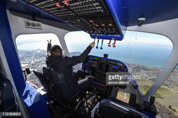 21 March 2019 BadenWuerttemberg Friedrichshafen Zeppelin pilot Lars Pentzek greets the photographer in the accompanying aircraft during the flight...