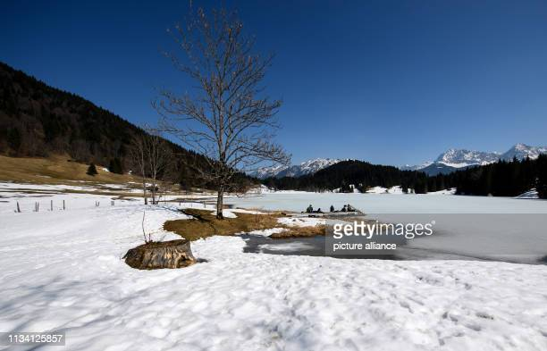 March 2019, Bavaria, Krün: Excursionists enjoy the beautiful weather on a jetty at the Geroldsee. Partly the lake is still frozen, the snow on the...