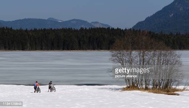 March 2019, Bavaria, Krün: Tourists push their bicycles through the snow on the shore of the Barmsee. Partly the lake is still frozen, the snow on...