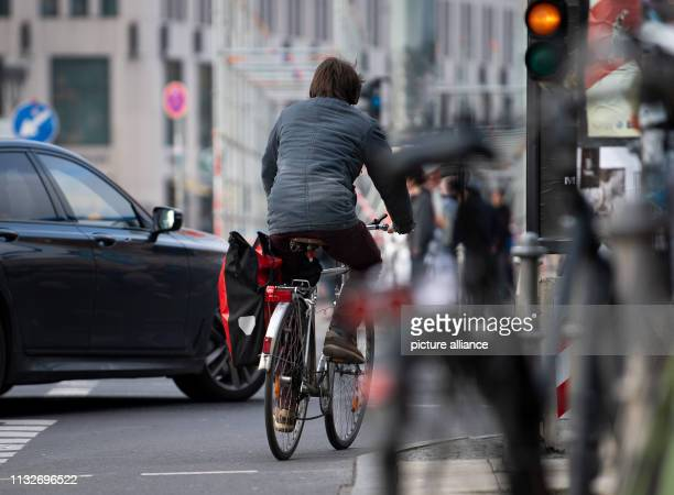 A cyclist drives past a car at an intersection on a cycle path Photo Monika Skolimowska/dpaZentralbild/dpa