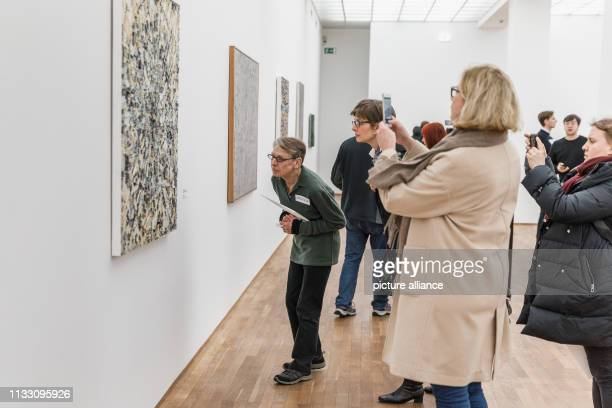"""March 2019, Berlin: People walk through the exhibition """"Jack Whitten. Jack's Jacks"""" with works by the American painter Jack Whitten at the Museum für..."""