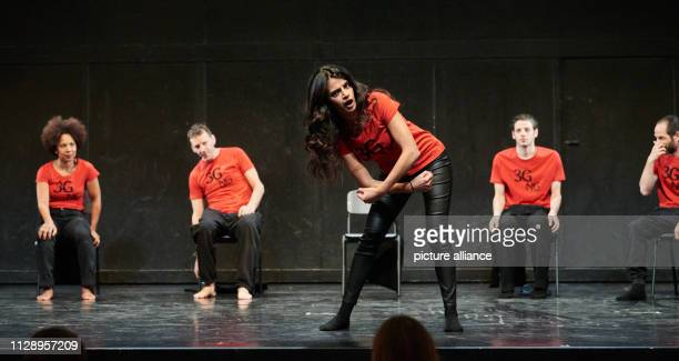 The actress Lamis Ammar performs on stage while in the background Abak SafaeiRad Knut Berger Karim Daoud and Yousef Sweid sit on chairs watching The...