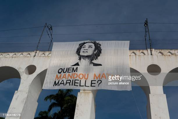 Who commissioned the murder of Marielle says a poster at a rally one year after the murder of prominent city councillor Marielle Franco and her...