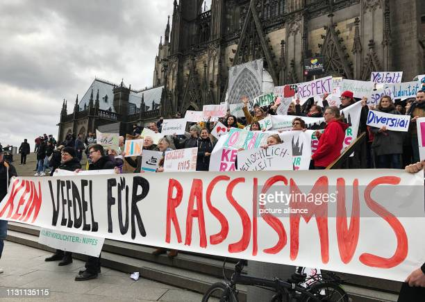 March 2019, Germany , Köln: Around 100 participants in a demonstration against racism and right-wing violence hold up banners in front of Cologne...
