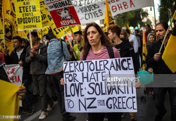 A woman at a demonstration against racism in the Greek capital wears a sign saying 'Zero tolerance for hatred Love and Solidarity for New Zealand...