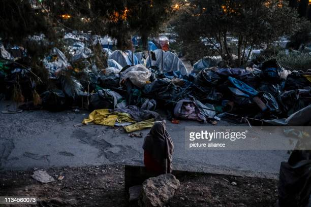A refugee is sitting in a refugee camp on the Greek island of Samos in front of a series of tents in the evening 4500 refugees and migrants live here...