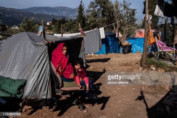 A woman sits in a refugee camp on the Greek island of Samos in front of her tent and holds her child in her arms Around 4500 refugees and migrants...