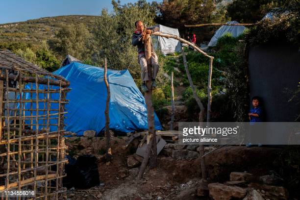 With the simplest means refugees build shelters in the camp on the Greek island of Samos to protect themselves from sun cold and rain Around 4500...
