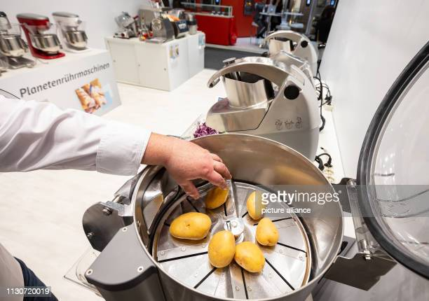 An employee of Dito Sama is demonstrating a vegetable peeling machine that peels 10 kilograms of potatoes in 40 seconds at the Internorga trade fair...