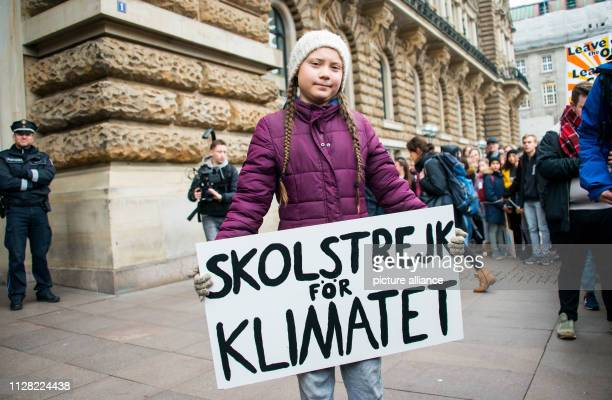 Greta Thunberg climate activist stands with a banner in front of a rally on the town hall market in front of the town hall The young Swedish woman...