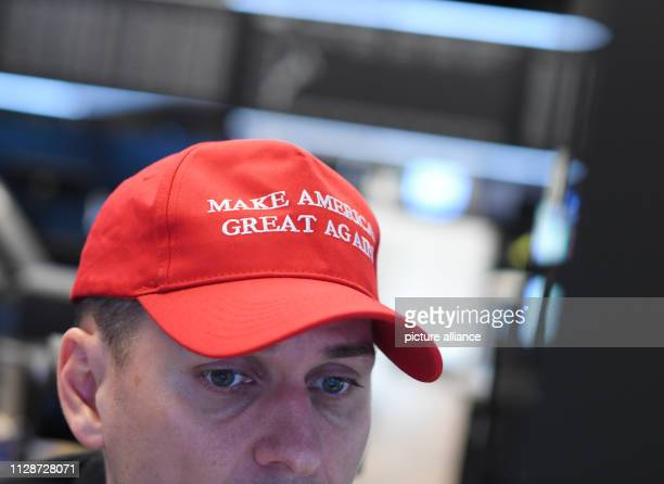 A stock trader wears a cap with the inscription Make America great again at his workplace on the floor of the Frankfurt Stock Exchange during the...
