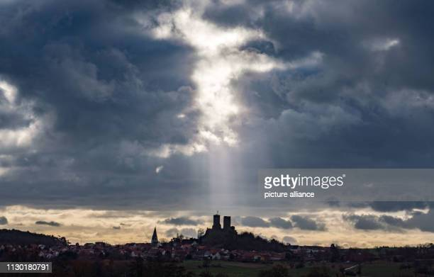 The two mountain peace lines of the castle Münzenberg in Mittelhessen visible from afar stand above the village of the same name in sunbeams that...