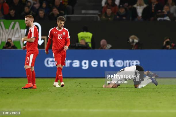 Soccer International match Germany Serbia in the Volkswagen Arena Ilkay Gündogan from Germany is painfully distorted on the field next to him are...