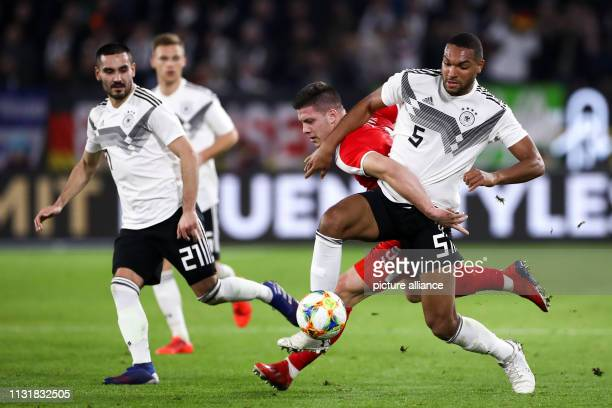 Soccer International match Germany Serbia in the Volkswagen Arena Germany's Jonathan Tah and Ilkay Gündogan in a duel with Luka Jovic from Serbia...