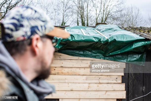 11 March 2019 North RhineWestphalia Mülheim an der Ruhr Andreas Kallweit looks at his garden house on whose roof a tree fell during the storm Andreas...