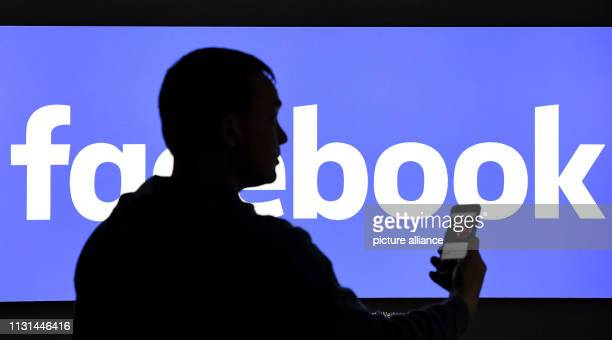 15 March 2019 SchleswigHolstein AukrugHomfeld ILLUSTRATION A man with a smartphone stands in front of a monitor with the Facebook logo Photo Carsten...