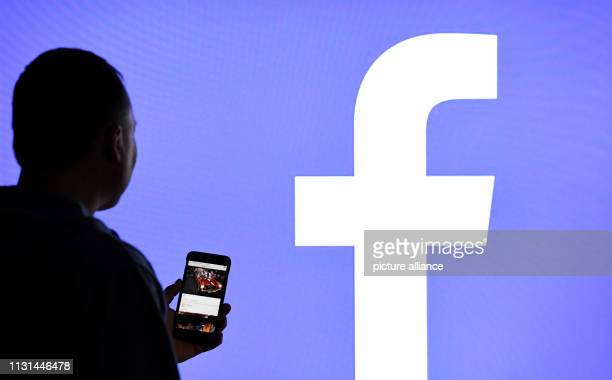 March 2019, Schleswig-Holstein, Aukrug-Homfeld: ILLUSTRATION - A man with a smartphone stands in front of a monitor with the Facebook logo. Photo:...