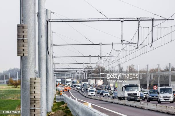 30 March 2019 SchleswigHolstein Reinfeld Cars and trucks drive past newly installed overhead line systems on the Autobahn 1 The expansion of the test...