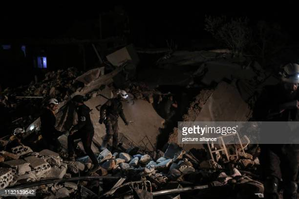 Members of the Syrian civil defence search for victims in the remains of a house allegedly targeted by an airstrike in the town of Kafraya in the...