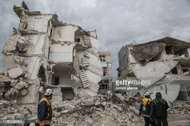 Syrian White Helmets inspect the rubble of a residential building that was struck during airstrikes believed to be mounted by Russian warplanes on...