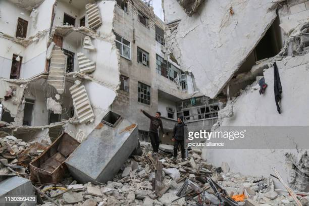 Syrians inspect the rubble of a residential building that was struck during airstrikes believed to be mounted by Russian warplanes on Wednesday Photo...