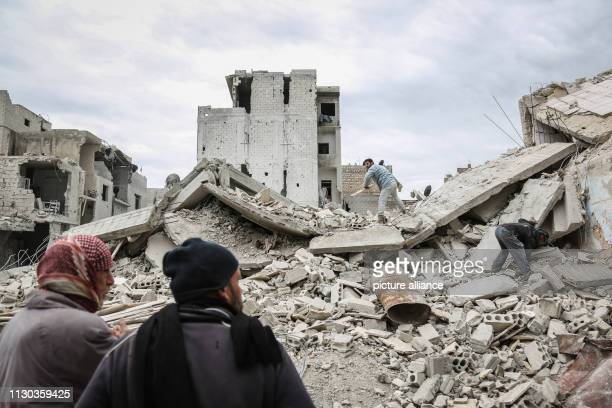 Syrians looks for salvageable goods in the rubble of a residential building that was struck during airstrikes believed to be mounted by Russian...