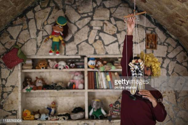Puppeteer Walid Rashed holds up a marionette puppet at his workshop where he prepares for his puppet acts for Syrian children on the occasion of the...