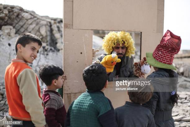 Puppeteer Walid Rashed performs a puppet act for Syrian children in the midst of the rubble of damaged buildings to mark the World Theatre Day as...