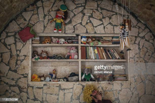 Puppeteer Walid Rashed smokes a cigarette under a shelf where he keeps his puppets at his workshop where he prepares for his puppet acts for Syrian...