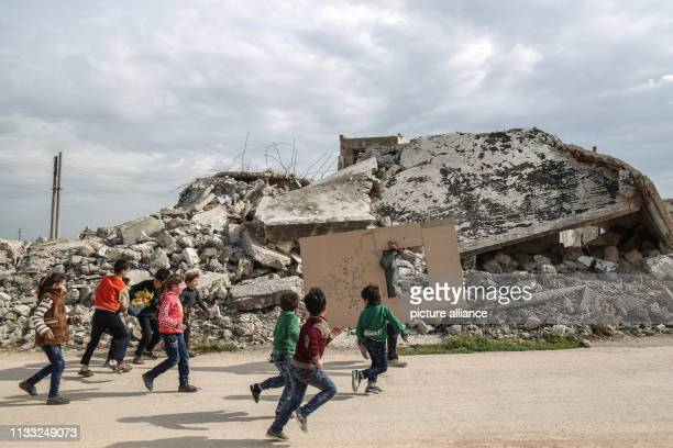 Syrian children follow puppeteer Walid Rashed past the rubble of a damaged building before performing a puppet act to mark the World Theatre Day as...
