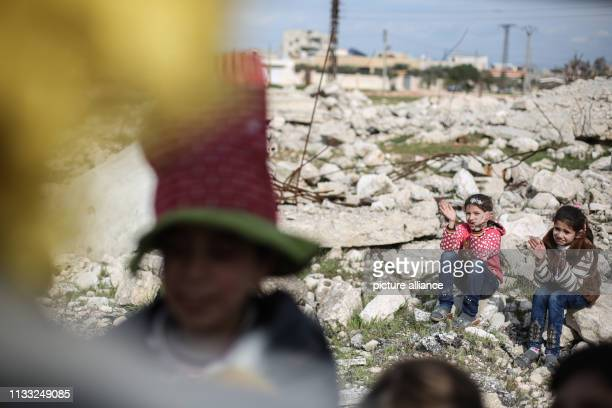 Syrian girls applaud as puppeteer Walid Rashed perform a puppet act in the midst of the rubble of damaged buildings to mark the World Theatre Day as...