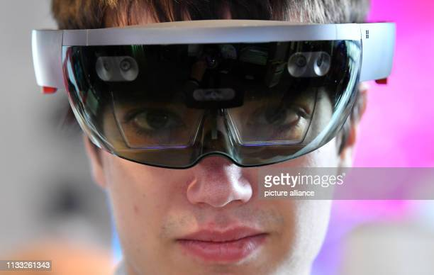 With a socalled HoloLens a young man looks at his environment at the Central German Fair for Digitisation in the Arena Erfurt Around 80 exhibitors...