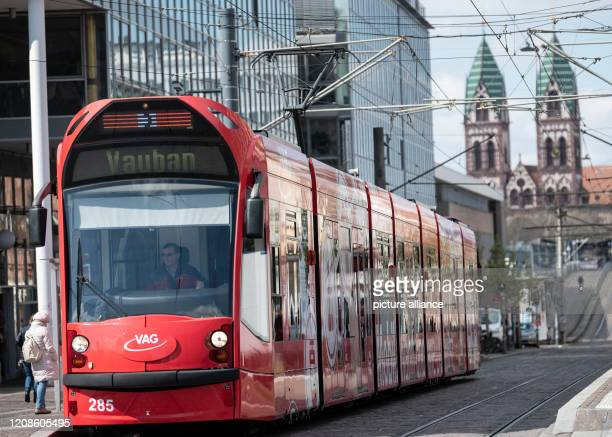 30 March 2020 BadenWuerttemberg Freiburg A tram runs in the city centre in front of the steeples of the HerzJesuKirche Due to the exit restrictions...