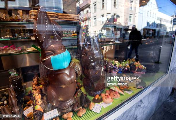 27 March 2020 BadenWuerttemberg Stuttgart A chocolate Easter bunny with a face mask stands in a shop window of a confectioner's shop reflecting...