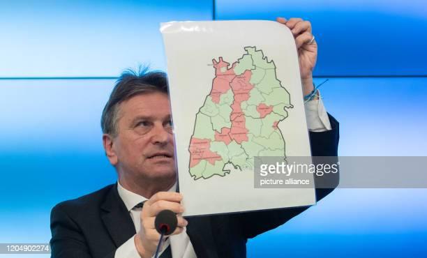 March 2020, Baden-Wuerttemberg, Stuttgart: Manfred Lucha , Minister of Social Affairs of Baden-Württemberg, holds a map of Baden-Württemberg in his...