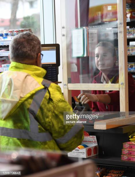 March 2020, Bavaria, Irschenberg: A saleswoman is standing in the gas station at the Irschenberg rest stop behind a Plexiglas panel at the cash desk....