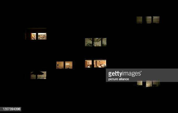 Light penetrates through the windows of apartments in a block of flats Due to the corona crisis life in Germany is now almost completely confined to...