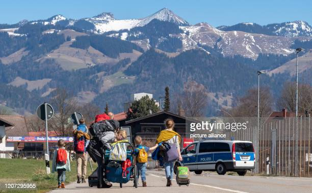 March 2020, Bavaria, Kiefersfelden: Two families with children, who had to end their journey by train in the Austrian town of Kufstein, walk with...