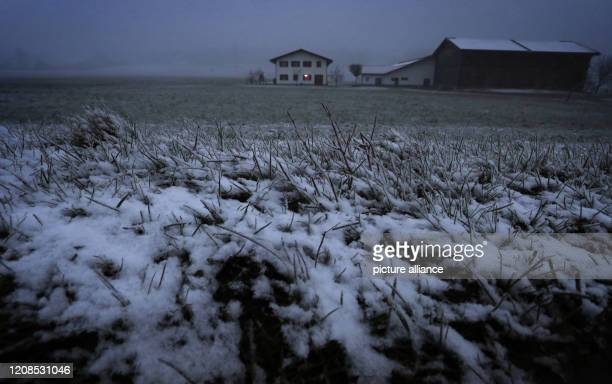 March 2020, Bavaria, Ruderatshofen: Snow lies on a meadow in front of a detached farm. Photo: Karl-Josef Hildenbrand/dpa