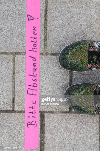 "March 2020, Berlin: In a bistro in the Volkspark Friedrichshain, pink strips with the inscription ""Please keep your distance"" are stuck on the floor...."