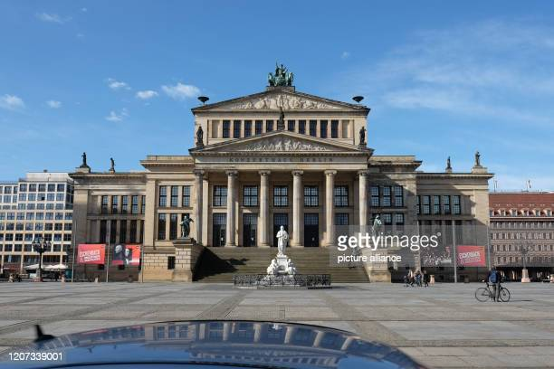 March 2020, Berlin: Only a few people go to the Gendarmenmarkt with the playhouse. The square is usually a popular place for tourists. In Berlin all...