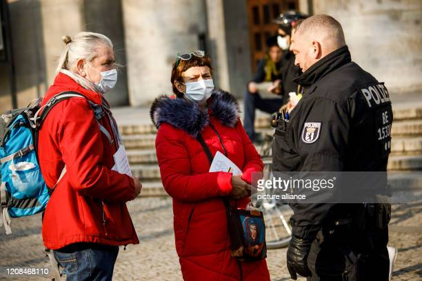 March 2020, Berlin: Participants wear face masks during a conversation with a policeman during a demonstration for constitution, basic law, as well...