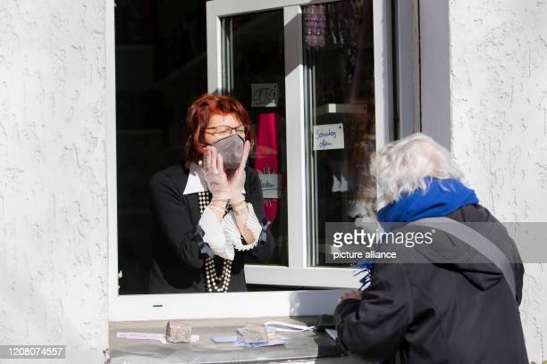 Pia Fischer textile artist sells protective masks to a customer from the window of her shop in BerlinSchöneberg The textile artist who normally makes...