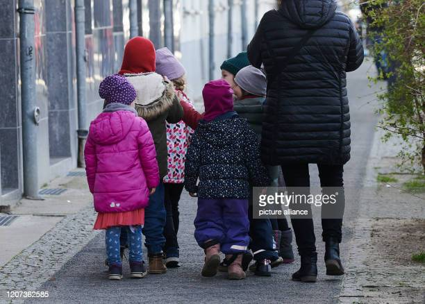 Some children walk on the pavement with a chaperone The kindergartens and daycare centres are closing this week because of the Corona epidemic There...