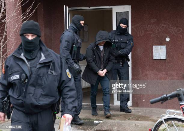 March 2020, Berlin: Two policemen lead a suspect away in Berlin-Mitte. In the course of a nationwide raid against a Vietnamese human trafficking...