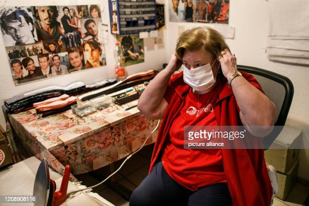 March 2020, Brandenburg, Strausberg: Kerstin Hiebsch, tailor, tests a mouth-nose mask after its completion in home work for the Berlin tie...